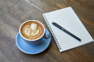 Coffee and note pad on table